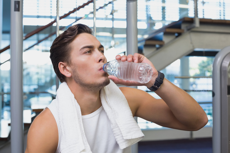 Fit man taking a drink while working out at the gym